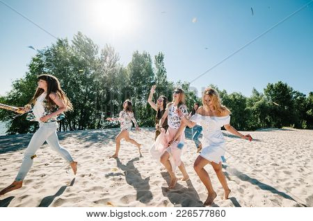 Beautiful Happy Stylish Sexy Young Girls Go Runs In Sand Beach Throwing Colored Confetti On Backgrou