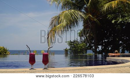 Two Glasses Cocktails On Background Of Pool, Sea, Palm Tree. Cocktails With Dragonfruit Near The Poo
