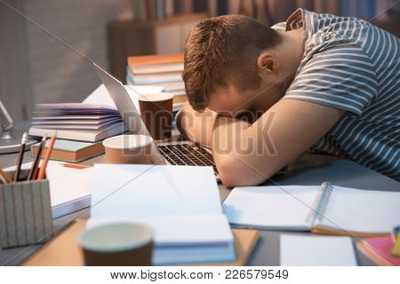 Tired student sleeping at table indoors
