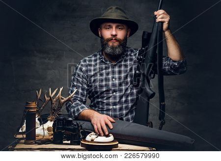 Studio Portrait Of A Bearded Traditional Hunter With His Trophy Holds A Rifle.