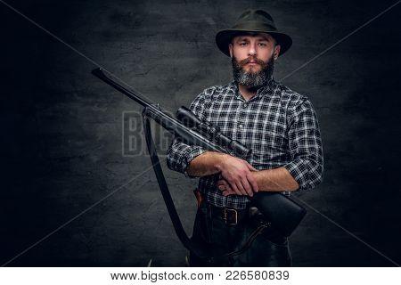 Studio Portrait Of A Bearded Hunter Holds A Rifle.