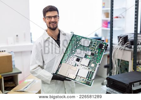Portrait Of Young Engineer Holding Cmts Network Card