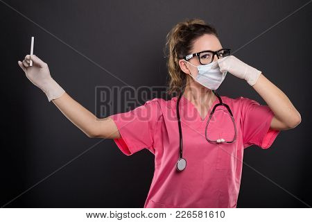 Portrait Of Attractive Lady Doctor Holding Cigarette Gesturing Bad Smell
