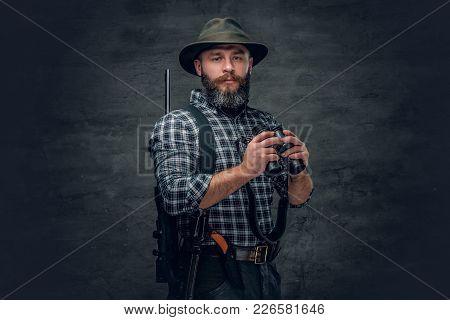Studio Portrait Of A Bearded Hunter Holds A Rifle And Binocular.