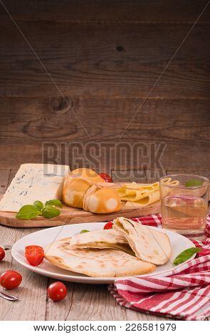 Cascione Italian Flatbread With Cheeses On White Dish.