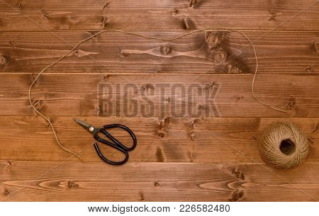 Ball Of Hessian Twine Unwound Across A Wooden Background To A Pair Of Black-handled Scissors - With