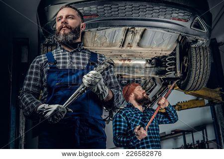 Two Brutal Bearded Mechanics Repairing A Car In A Garage.