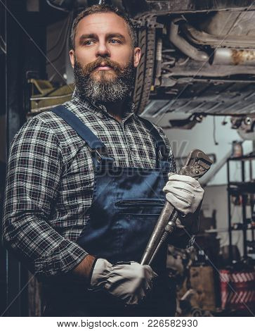 Portrait Of Bearded Mechanical Male In A Garage.