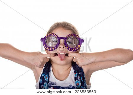 Little girl with silly glasses on making a face and sticking out tongue.