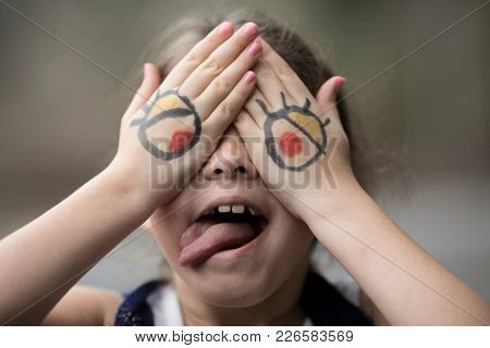 Little girl with cartoon eyes painted on her hands making silly face.