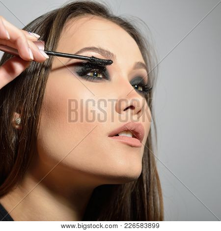 Young beautiful model applying makeup. Fashion girl with mascara. Eyelash makeup. Fashion girl.