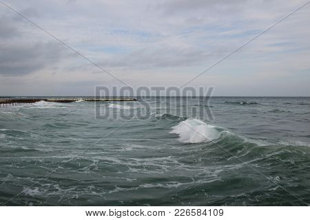 Empty Beach Of The North Sea In Cloudy Autumn Weather. Landscape With Stormy Sea Waves Break About T