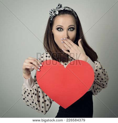 Beautiful girl holding large paper red heart and closing her mouth with hand. Heartbreaker. Temptress. Seductive woman. Portrait of funny pinup young fashion woman posing at studio. Love. Valentine's