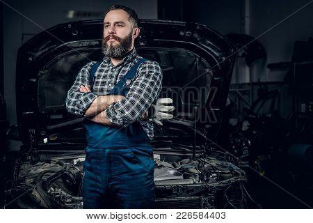 Portrait Of Bearded Mechanic Man Near The Car In A Garage.