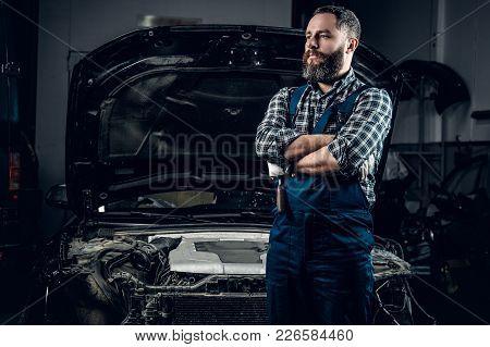 Portrait Of Bearded Mechanic In Front Of A Car In A Garage.