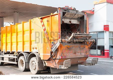 Rear End Of Garbage Dumper Truck On The Way To Waste Dumpster Cans Ready To Collect Litter And Junk