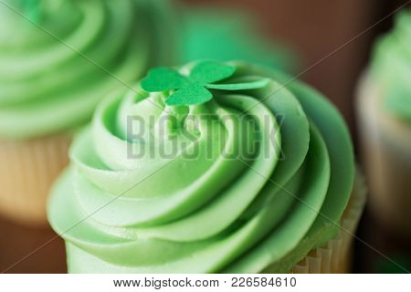 st patricks day, food and bakery concept - close up of green frosted cupcake with shamrock decoration on top