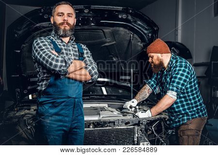 Two Bearded Men Repairing A Car In A Garage.