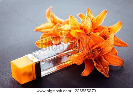 Bottle Of Perfume With Lily On Black Background