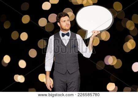 fashion, style and communication concept - concerned man in suit holding blank text bubble banner over lights on black background