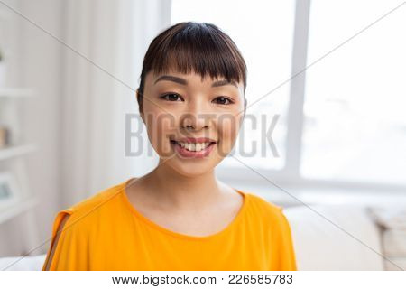 people, portrait and ethnicity concept - happy asian young woman at home