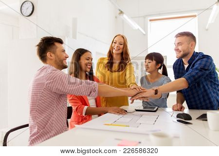 business, architecture, teamwork and people concept - happy international creative architect team or students with blueprint putting hands on top together at office