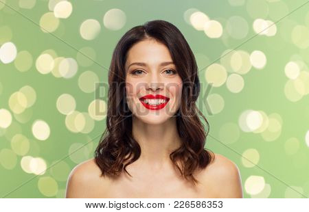beauty, make up and people concept - happy smiling young woman with red lipstick over green background with lights