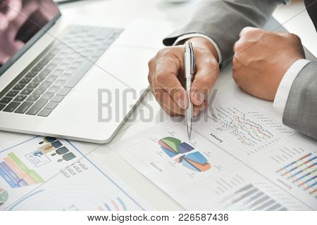 Businessman Hand Is Pointing On Business Chart Or Graph Documents With A Pen. Man In Grey Suit And B