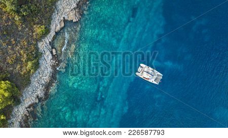 Aerial view of anchoring catamaran next to the island. Ocean and sea travel and transportation