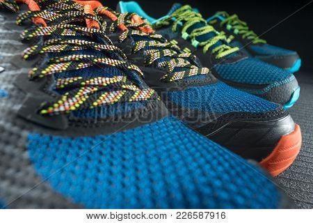 Two Pairs Of Colourful Exercise Trainers / Running Shoes Inside A Gym Or Shoe Shop. Potential Copy S