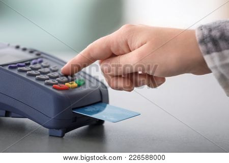 Woman using bank terminal for credit card payment at table