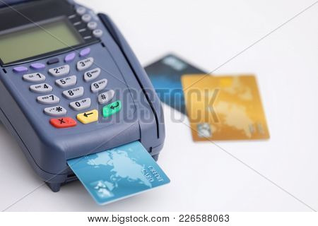 Credit card and bank terminal on white background