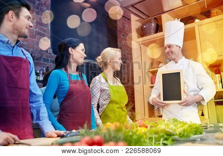 cooking class, culinary, food and people concept - happy friends and chef cook with blank menu chalk board in kitchen