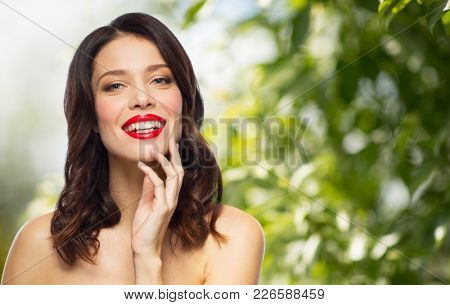 beauty, make up and people concept - happy smiling young woman with red lipstick posing over green natural background