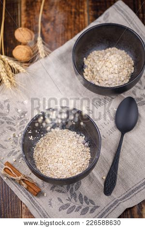 Delicious And Light Breakfast. Leavening In A Bowl Of Dry Flakes Of Oatmeal. Still-life On A Wooden