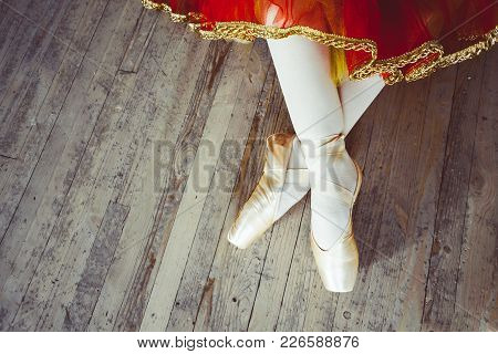 Beautiful Legs Of Young Ballerina Who Puts On Pointe Shoes At White Wooden Floor Background, Top Vie