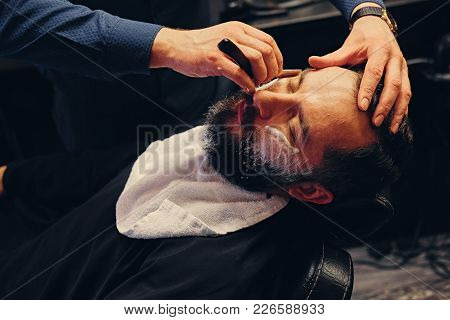 Close Up Portrait Of Barber Shaving Bearded Male With A Sharp Razor In A Saloon.