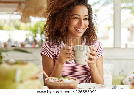 Photo Of Positive Dark Skinned Mixed Race Female Ejoys Good Rest At Coffee Shop, Drinks Hot Beverage