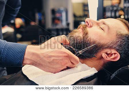 Stylish Barber Grooming A Man's Beard In A Saloon.
