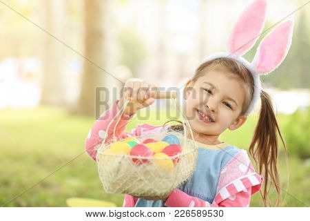 Cute little girl with basket of colorful eggs in park. Easter hunt concept