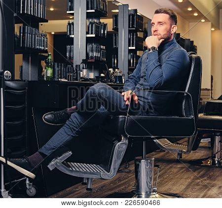 Portrait Of Stylish Male Sits On A Chair In Hairdresser Saloon.