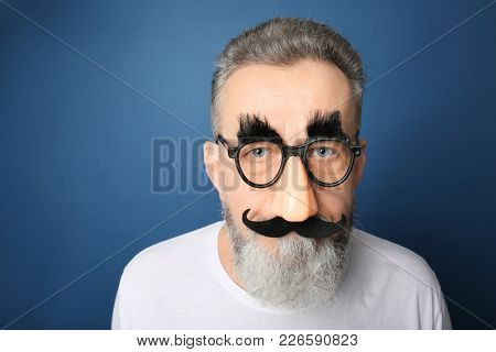 Mature man in funny disguise on color background. April fool's day celebration