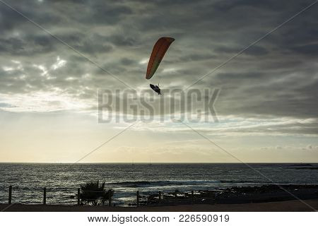 A Glider With Orange Wings On The Background Of The Sea Landscape At Sunset