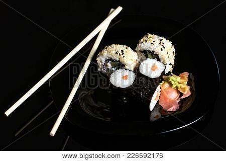 Sushi Rolls In Plate Over Black Background
