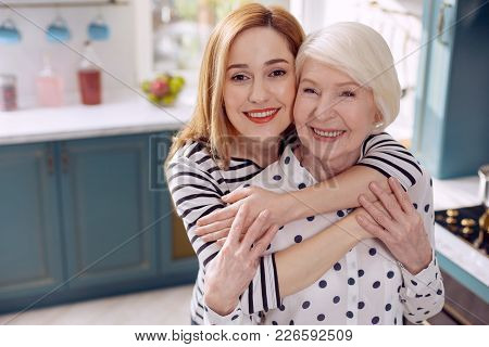 Daughterly Love. Cheerful Young Woman Hugging Her Elderly Mother And Smiling At The Camera Happily T