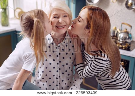 Love Our Granny. Cute Little Girl And Her Mother Kissing A Senior Woman On The Cheeks Together While