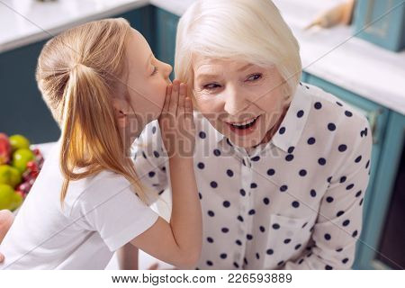 Keep My Secret. Pretty Little Girl Whispering In The Ear Of Her Grandmother, Sharing Her Secrets Wit