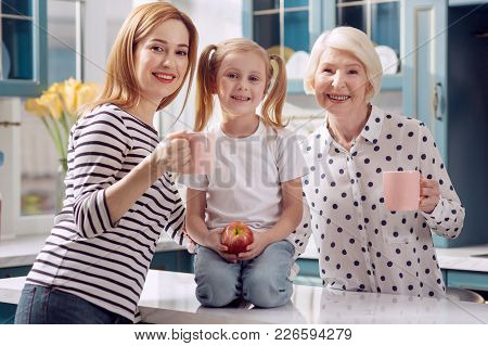 Happy Relatives. Adorable Little Girl Sitting On The Kitchen Counter And Holding An Apple While Her