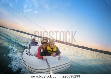 Happy Couple With Daughter Riding Boat On Lake Or River At Sunset. Pair  With Child Making Selfie Wh