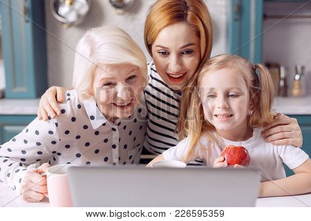 Family Call. Three Generations Of Females Sitting At The Kitchen Counter And Smiling At The Web Came